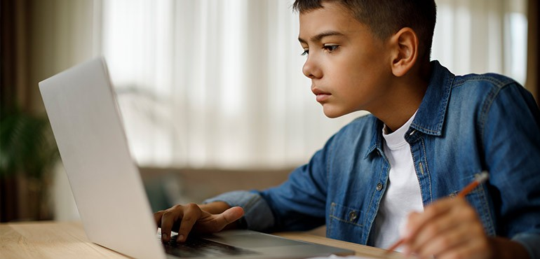 A young boy looks intently at his laptop.